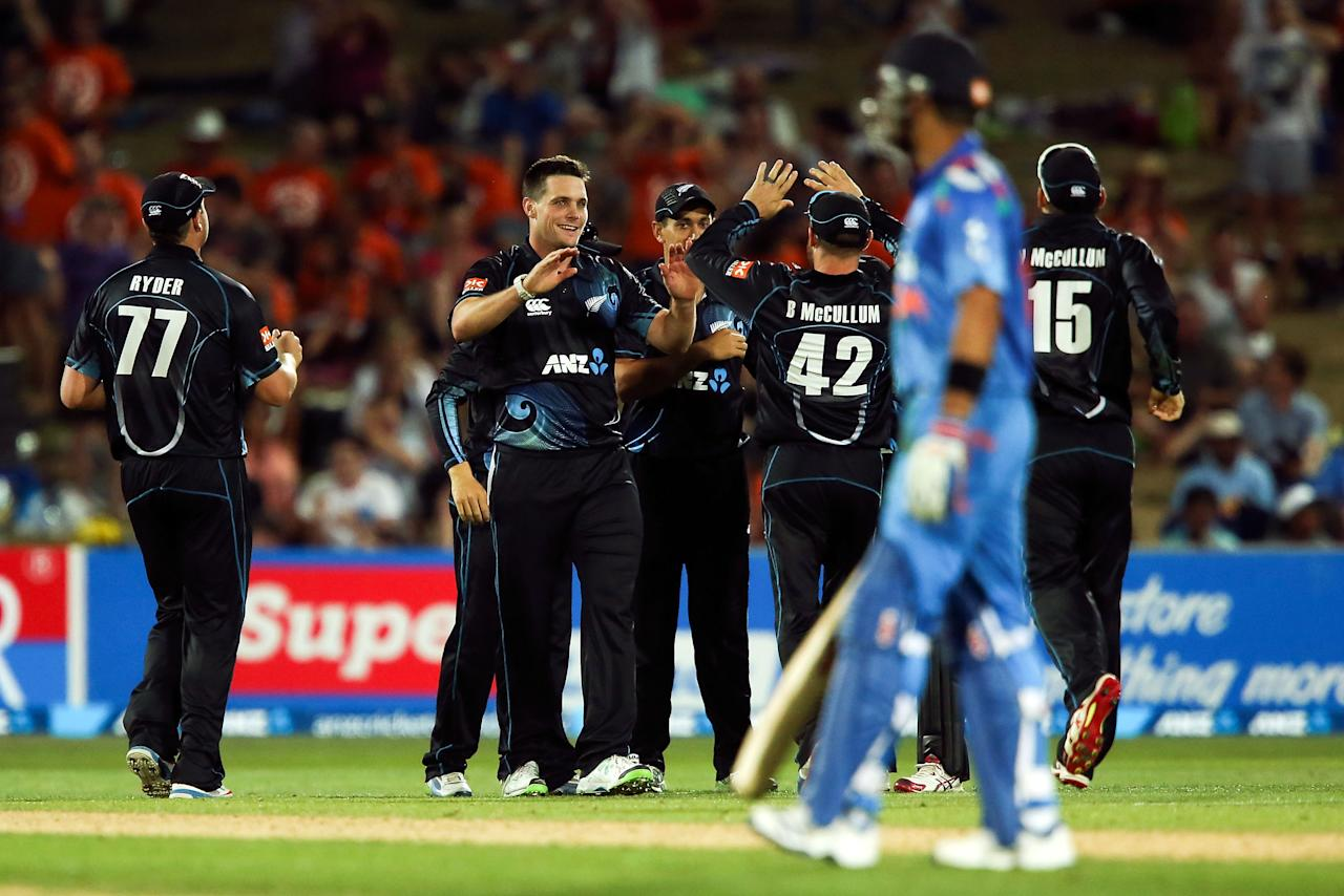 NAPIER, NEW ZEALAND - JANUARY 19:  Mitchell McClenaghan of New Zealand celebrates with teammates Brendon McCullum after taking the wicket of MS Dhoni of India during the first One Day International match between New Zealand and India at McLean Park on January 19, 2014 in Napier, New Zealand.  (Photo by Hagen Hopkins/Getty Images)
