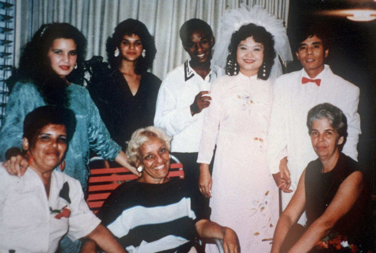 In this 1992 photo provided by Phan Thi Kim Phuc shows her, top row second from right, and her husband Bui Huy Toan, top row right, with guests during their wedding day in Havana, Cuba. It only took a second for Associated Press photographer Nick Ut to snap the iconic black-and-white image of her after a napalm attack in 1972. It communicated the horrors of the Vietnam War in a way words could never describe, helping to end one of America's darkest eras. But beneath the photo lies a lesser-known story. It's the tale of a dying child brought together by chance with a young photographer. A moment captured in the chaos of war that would serve as both her savior and her curse on a journey to understand life's plan for her. (AP Photo/Courtesy Phan Thi Kim Phuc)
