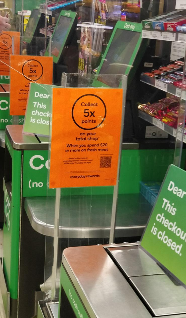 A promotional sign at Woolworths offering Rewards points for fresh meat purchases.
