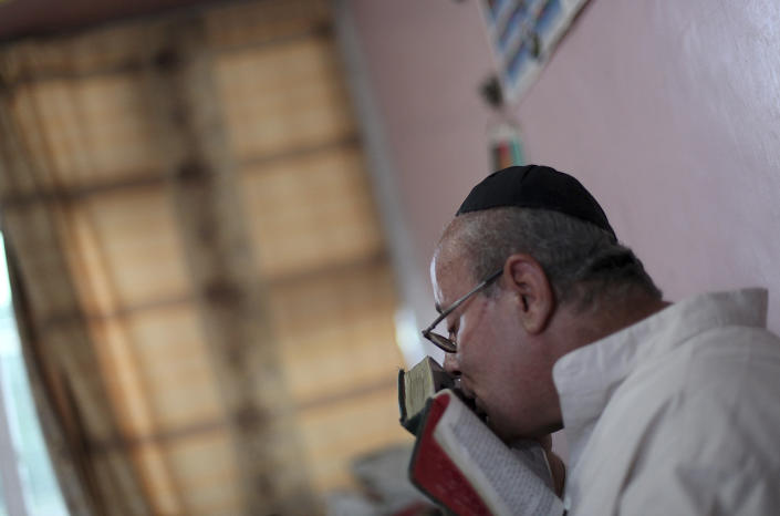 FILE - In this Aug. 29, 2009 file photo, Zebulon Simentov, the last known Jew living in Afghanistan and the caretaker and sole member of Afghanistan's only working synagogue kisses his prayer book while observing Shabbat in his Kabul home. Simentov who prayed in Hebrew, endured decades of war as the country's centuries-old Jewish community rapidly dwindled has left the country. The Taliban takeover in August, 2021, seems to have been the last straw. (AP Photo/David Goldman, File)