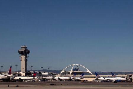 United Airlines planes are seen in the foreground of the Los Angeles International Airport (LAX) and its air traffic control tower on February 20, 2013. Picture taken on February 20, 2013. REUTERS/Adrees Latif/Files