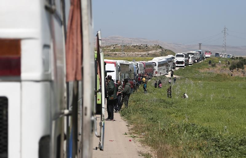 A convoy transporting Syrian civilians and rebel fighters evacuated from Eastern Ghouta waits in a government-held area prior to entering the village of Qalaat al-Madiq, some 45 kilometres northwest of the central city of Hama, on March 26, 2018 (AFP Photo/ABDULMONAM EASSA)