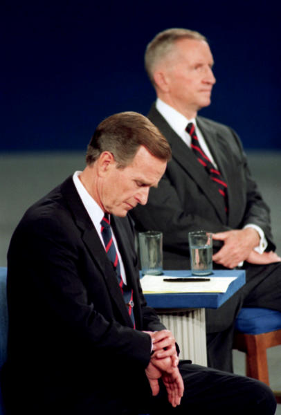 FILE - In this Oct. 15, 1992, file photo President George H.W. Bush looks at his watch during the 1992 presidential campaign debate with other candidates, Independent Ross Perot, top, and Democrat Bill Clinton, not shown, at the University of Richmond, Va. They spend hours mastering policy. Learning to lean on the podium just so. Perfecting the best way to label their opponents as liars without whining. But presidential candidates and their running mates often find that campaign debates turn on unplanned zingers, gaffes or gestures that speak volumes. Debate wins and losses often are scored based on the overall impressions that candidates leave with voters. In the history books, though, small debate moments often end up telling the broader story. (AP Photo/Ron Edmonds, File)