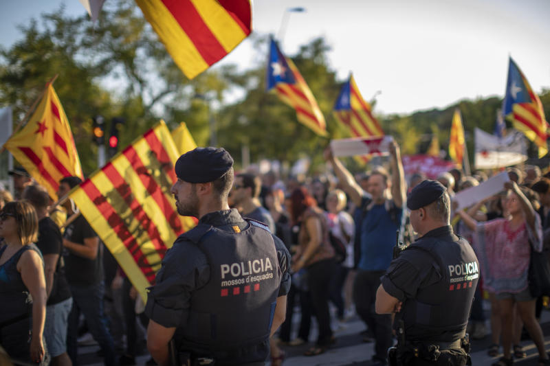 Catalan police officers stand guard as pro-independence demonstrators march during a protest in Sabadell, near Barcelona, Spain, Saturday, Sept. 28, 2019. Several thousand people have marched in a town near Barcelona to protest the jailing of seven Catalan separatists for allegedly planning to commit violent acts of terrorism with explosives. (AP Photo/Emilio Morenatti)