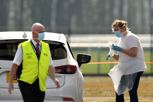 A medical worker tests a NHS worker at a drive-in testing station at Haydock Park Racecourse in Merseyside (Picture: Getty)