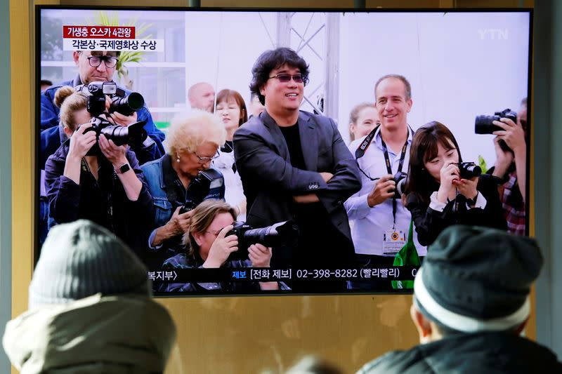 "FILE PHOTO: People watch a TV broadcasting a news report on South Korean director Bong Joon-ho who won four Oscars with his film ""Parasite"", in Seoul"