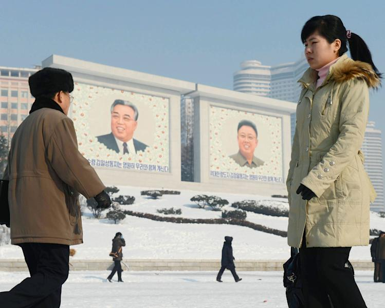 North Koreans walk by the portraits of North Korea's national founder Kim Il Sung, left, and late leader Kim Jong Il in Pyongyang, North Korea Monday, Dec. 10, 2012. North Korea on Monday extended the launch period for a controversial long-range rocket by another week until Dec. 29, citing technical problems. (AP Photo/Kyodo News) JAPAN OUT, MANDATORY CREDIT, NO LICENSING IN CHINA, FRANCE, HONG KONG, JAPAN AND SOUTH KOREA