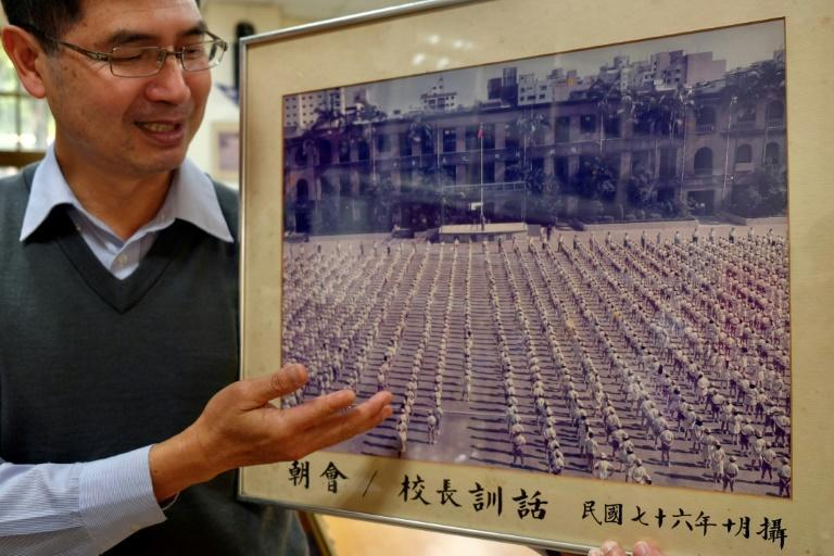 Lin Ming-ju, principal of Taipei's Laosong Elementary School, shows a photograph taken in 1987 showing students at the school stadium