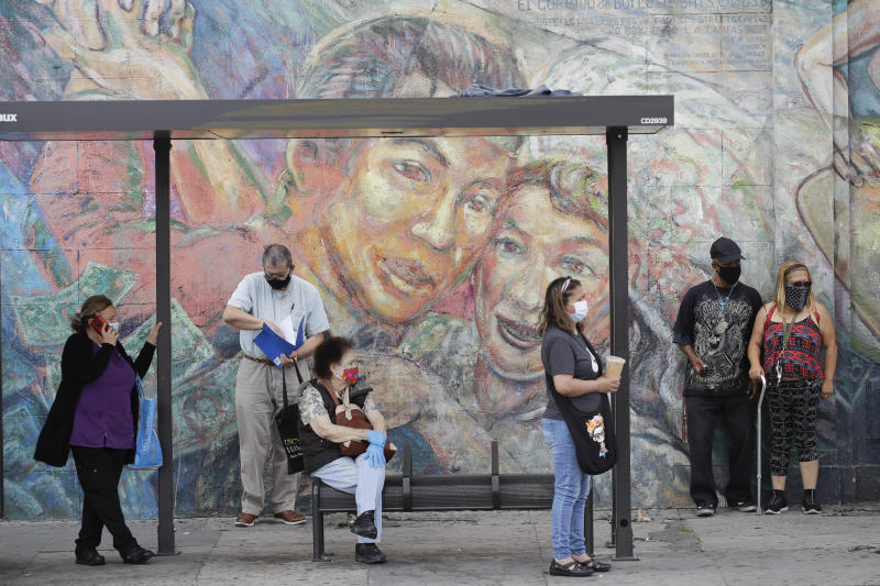 People wear masks as they wait at a bus stop amid the coronavirus pandemic Monday, June 29, 2020, in Los Angeles. (AP Photo/Marcio Jose Sanchez)