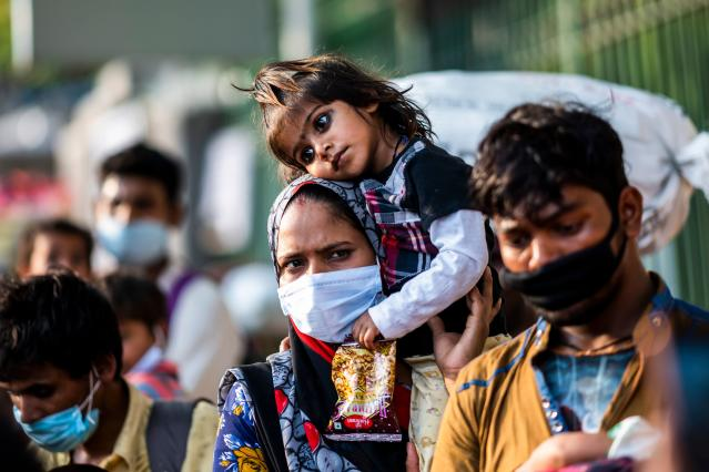 A migrant worker mother carries her daughter on her shoulder as she walks along a street during a nationwide lockdown imposed as a preventive measure against the spread of the COVID-19 coronavirus in New Delhi on May 13, 2020. (Photo by Jewel SAMAD / AFP) (Photo by JEWEL SAMAD/AFP via Getty Images)