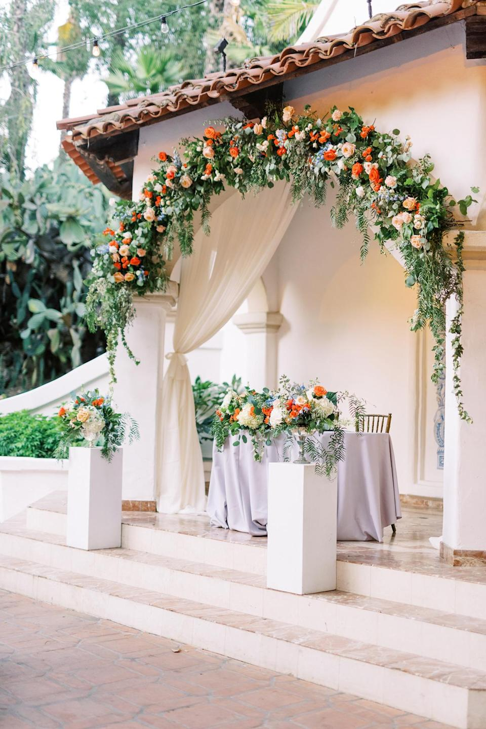 <p>During the reception, Ana and Charles sat at a sweetheart table—in the exact spot where they'd exchanged their promises just hours ago. Florals corresponding to the garland of blooms above were added to the edge of their station.</p>