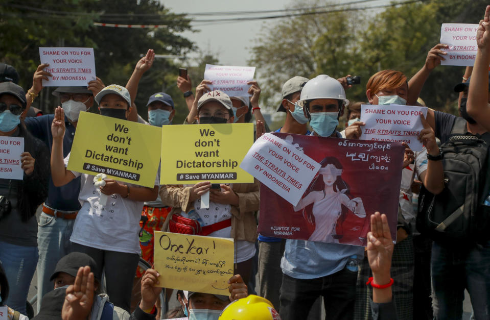 Demonstrators display placards during a protest close to Indonesian Embassy in Yangon, Myanmar Tuesday, Feb. 23, 2021. Anti-coup protesters gathered outside the Indonesian Embassy following reports that Indonesia was seeking to have fellow members of the Association of Southeast Asian Nations to agree on an action plan over the Myanmar's coup that would hold the junta to its promise to hold free and fair elections in a year's time. The Indonesia Foreign Ministry has denied the report. (AP Photo)