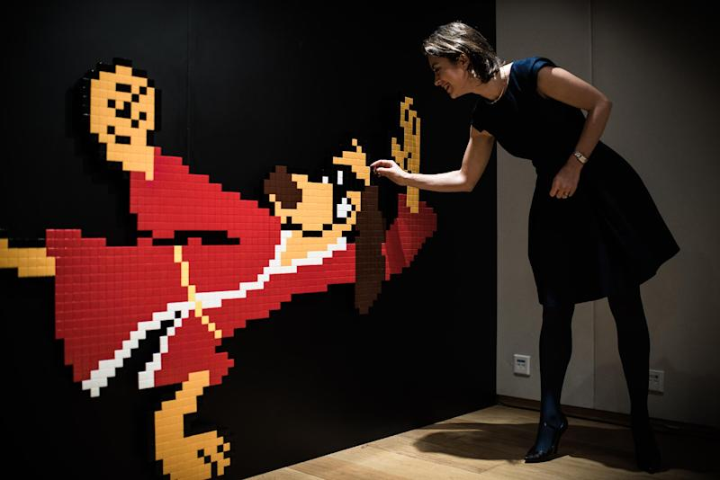 An employee of Sotheby's stands next to a ceramic mosaic of 1970s US cartoon character Hong Kong Phooey created by French street artist Invader, on January 15, 2015