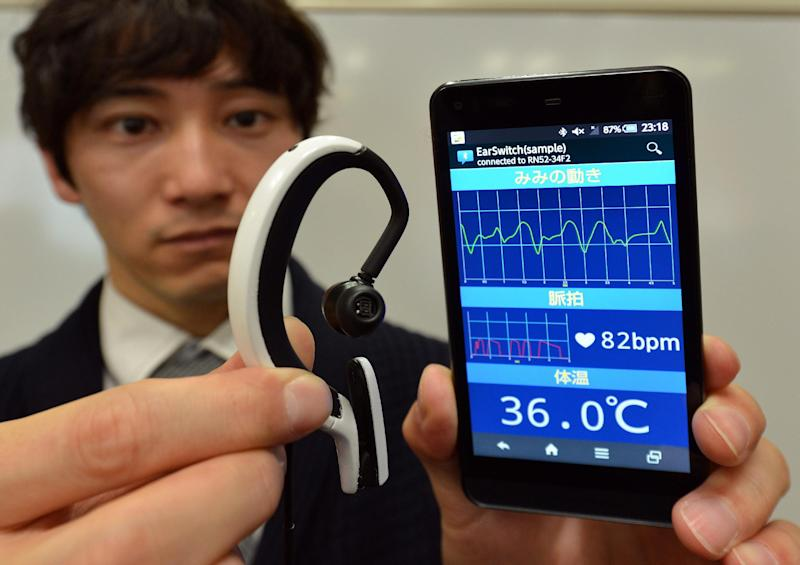 """Engineer from Japanese machinery maker NS West shows the """"Earclip-type Wearable PC"""" equipped with sensors such as a pulse meter and thermometer and bluetooth wireless communication, in Tokyo on February 20, 2014 (AFP Photo/Yoshikazu Tsuno)"""