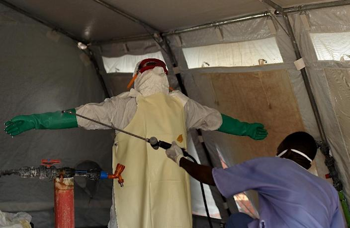 A nurse wearing personal protective equipment (PPE) is spayed with desinfectant before leaving the red zone at the Kenama ebola treatment center run by the Red Cross Society on November 15, 2014 (AFP Photo/Francisco Leong)