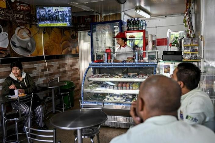 Customers of a bakery in Medellin, Colombia, watch a broadcast on August 29, 2019 of a video posted on YouTube of a former senior FARC commander announcing he is taking up arms again (AFP Photo/Joaquin SARMIENTO)