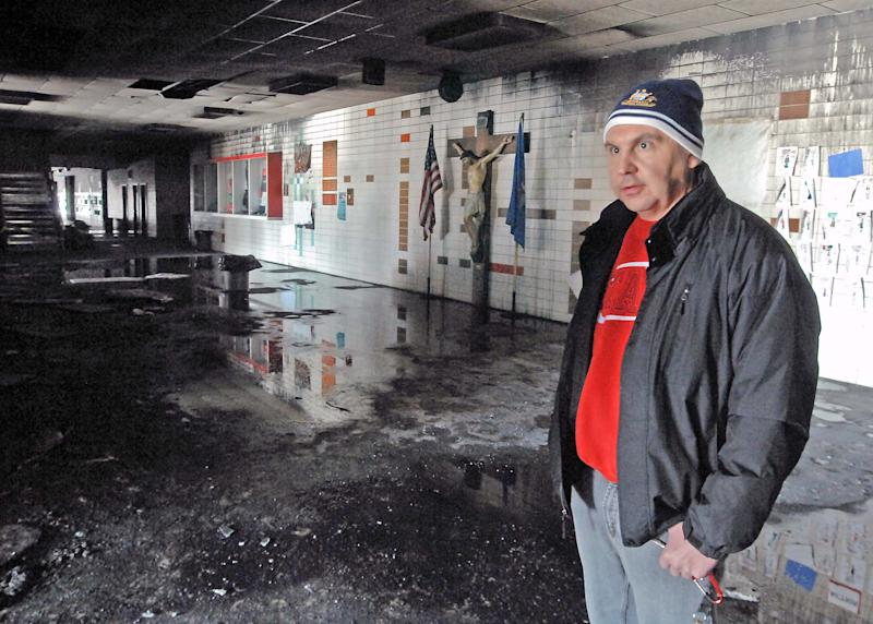 Dickinson Catholic School vice president Rev. Patrick Schumacher stands inside the fire damaged Trinity High School on Wednesday, March 5, 2014. The high school suffered major damage from the fire and will not be in use for the duration of the school year. (AP Photo/The Tribune, Tom Stromme)