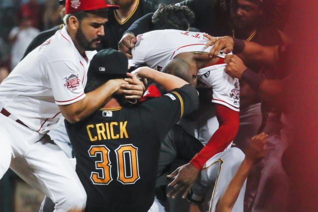 Pittsburgh Pirates' Kyle Crick (30) and Cincinnati Reds' Eugenio Suarez, left, and Amir Garrett, center right, are part of a brawl during the ninth inning of a baseball game Tuesday, July 30, 2019, in Cincinnati. (AP Photo/John Minchillo)