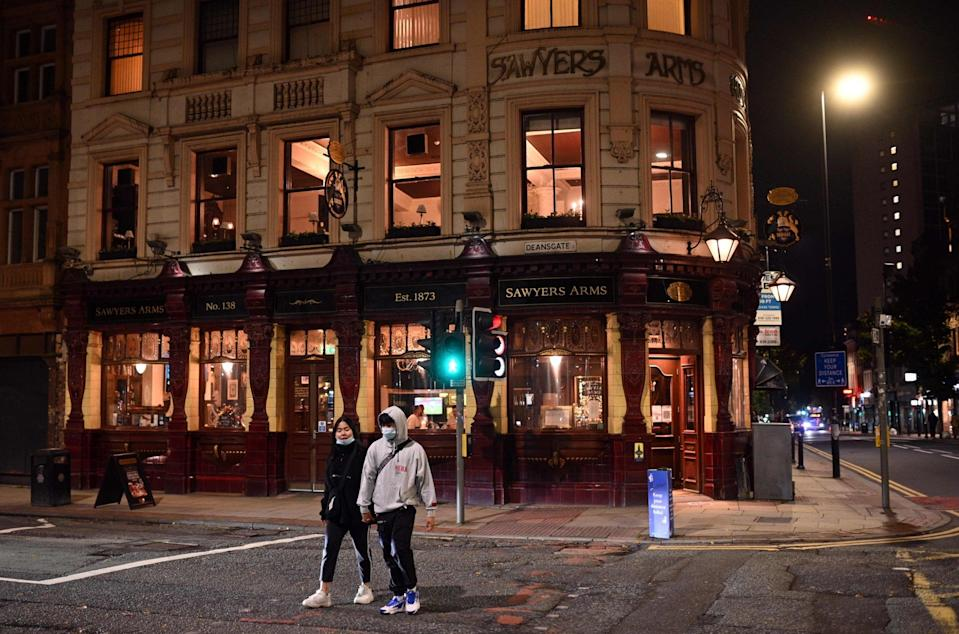 People wearing face masks walk past a quiet pub in the city centre of Manchester: AFP via Getty Images