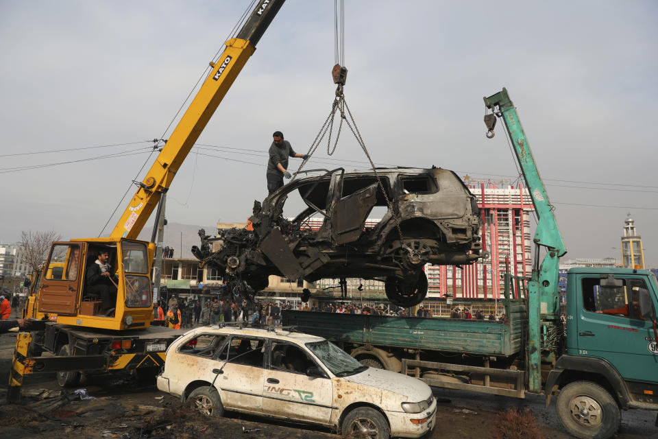 Afghan security personnel oversee the removal of damaged vehicles after a bombing attack in Kabul, Afghanistan, Sunday, Dec. 20, 2020. Afghanistan's Interior Ministry says that the car bomb blast killed at least eight people and wounded more than 15 others, including a member of parliament, Khan Mohammad Wardak. (AP Photo/Rahmat Gul)