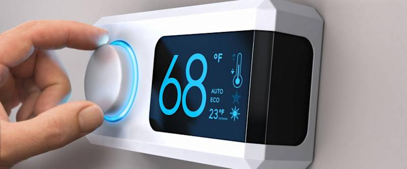 Hand turning a home thermostat knob to set temperature on energy saving mode.