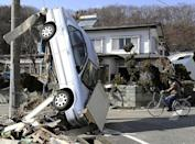 A car leans against a wire from an electric pole in Miyako, northeastern Japan, Saturday, March 12, 2011, one day after an 8.9-magnitude quake and the tsunami it spawned hit the country's northeastern coast. (AP Photo/Kyodo News)