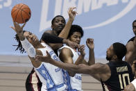 North Carolina forward Armando Bacot (5) and guard Kerwin Walton struggle with Florida State forward Malik Osborne (10) and center Tanor Ngom, rear, during the first half of an NCAA college basketball game in Chapel Hill, N.C., Saturday, Feb. 27, 2021. (AP Photo/Gerry Broome)