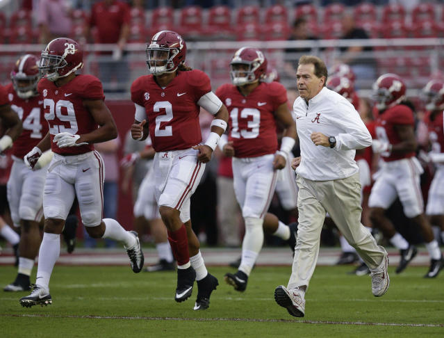 """FILE – In this Saturday, Oct. 14, 2017, file photo, Alabama coach Nick Saban and quarterback <a class=""""link rapid-noclick-resp"""" href=""""/ncaaf/players/264323/"""" data-ylk=""""slk:Jalen Hurts"""">Jalen Hurts</a> (2) runs onto the field before the team's NCAA college football game against Arkansas in Tuscaloosa, Ala. No. 1 Alabama and No. 3 Georgia are on track to give the SEC two undefeated teams in the championship game for the first time since 2009. (AP Photo/Brynn Anderson, File)"""