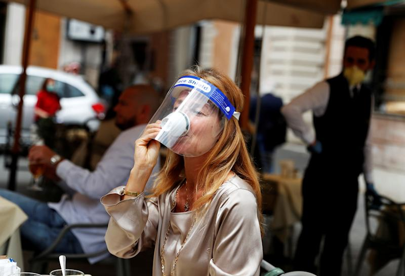 A woman wearing a face shield drinks coffee at a cafe as Italy eases some of the lockdown measures put in place during the coronavirus disease (COVID-19) outbreak, in Rome, Italy May 18, 2020. REUTERS/Yara Nardi TPX IMAGES OF THE DAY (Photo: Yara Nardi / Reuters)