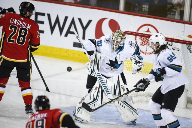 San Jose Sharks goalie Aaron Dell, right, deflects a shot from Calgary Flames' Elias Lindholm during the second period of an NHL hockey game, Tuesday, Feb. 4, 2020 in Calgary, Alberta. (Jeff McIntosh/The Canadian Press via AP)