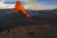 People watch as lava flows from an eruption from the Fagradalsfjall volcano on the Reykjanes Peninsula in southwestern Iceland on Tuesday, May 11, 2021. The glow from the bubbling hot lava spewing out of the Fagradalsfjall volcano can be seen from the outskirts of Iceland's capital, Reykjavík, which is about 32 kilometers (20 miles) away. Pandemic or no pandemic, the world will never stand still. That's perhaps no clearer than in Iceland where the Fagradalsfjall volcano has awoken from a slumber that has lasted 6,000 years, give or take a year or two. (AP Photo/Miguel Morenatti)