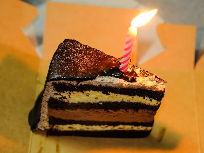 A slice of a birthday cake with a lit candle on it