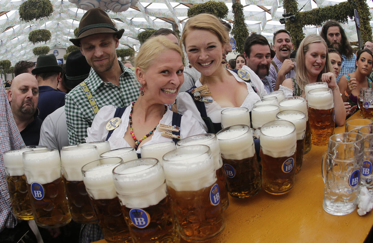 FILE - In this Sept. 20, 2014 file photo waitresses Beli, right, and Anika pose with beer mugs during the opening of the 181th Oktoberfest beer festival in Munich, Germany. Munich's city council has voted down an attempt to cap foaming beer prices at the annual Oktoberfest. Deputy mayor Josef Schmid, who oversees the Bavarian capital's annual beer extravaganza, had sought a legal cap for the next three years on the price of the traditional Mass, a one-liter (two-pint) glass of beer. Schmid failed to secure a majority for his plan at a council meeting Wednesday, May 17, 2017 news agency dpa reported. (AP Photo/Matthias Schrader,file)
