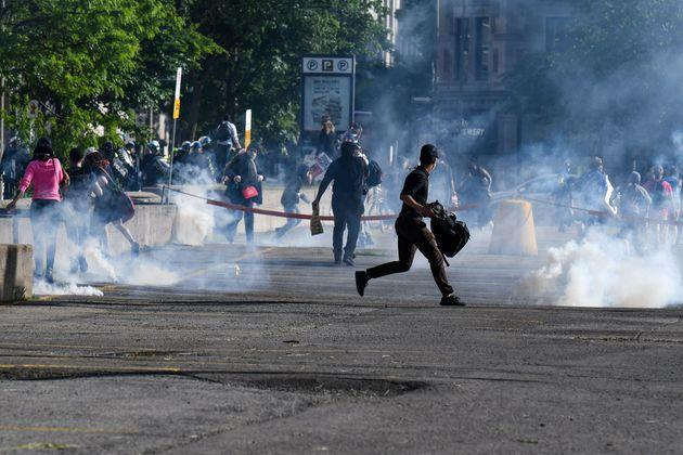 Demonstrators are running as Montreal Police uses tear gas during a march against police brutality and racism in Montreal, Canada, on June 7, 2020.