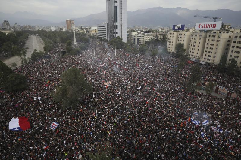 FILE - In this Oct. 25, 2019 file photo, anti-government protesters fill Plaza Italia in Santiago, Chile. Student protests over a fare hike morphed into a nationwide call for socio-economic equality and better social services that brought millions to the streets and forced President Sebastián Piñera to increase benefits for the poor and disadvantaged and start a process of constitutional reform. (AP Photo/Rodrigo Abd, File)