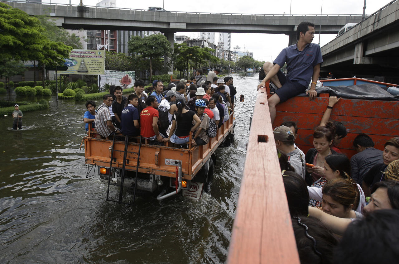Thai residents ride on a truck as they move to higher grounds in Bangkok, Thailand, Saturday, Oct. 29, 2011. 2011. The complex network of flood defenses erected to shield Thailand's capital from the country's worst floods in nearly 60 years was put to the test Saturday as coastal high tides hit their peak. (AP Photo/Aaron Favila)