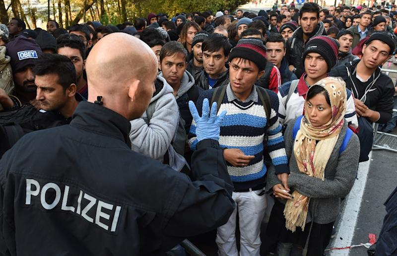 A German police officer speaks with migrants waiting to cross the Austrian-German border near the Bavarian town of Passau, southern Germany, on October 28, 2015 (AFP Photo/Christof Stache)