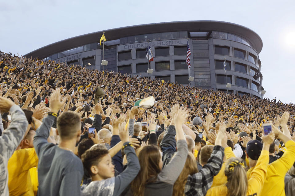 FILE - In this Saturday, Aug. 31, 2019 file photo, Iowa fans wave to children in the University of Iowa Stead Family Children's Hospital at the end of the first quarter of an NCAA college football game between Iowa and Miami of Ohio in Iowa City, Iowa. During a season when the atmosphere will be subdued at Iowa home football games because the usual 69,000 fans won't be there, one tradition will go on uninterrupted. At the end of the first quarter, players and coaches from both teams will turn to the University of Iowa Stead Family Children's Hospital and wave, just as they've done every home game since 2017.( (AP Photo/Charlie Neibergall, File)