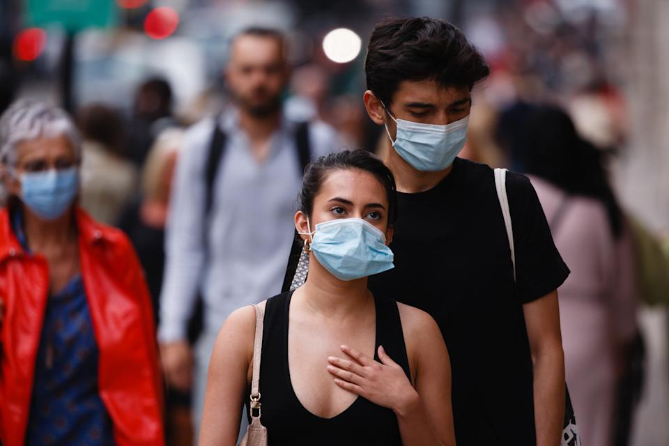 A man and woman wearing face masks walk along Regent Street in London, England, on September 22, 2020. British Prime Minister Boris Johnson this afternoon announced a raft of new coronavirus restrictions to apply across England, possibly to last the next six months, including requiring pubs and restaurants to close at 10pm and for retail staff to all wear face masks. A return to home working where possible is also being encouraged. The new measures come amid fears of a 'second wave' of covid-19 deaths prompted by rising numbers of people testing positive in recent weeks. (Photo by David Cliff/NurPhoto via Getty Images)