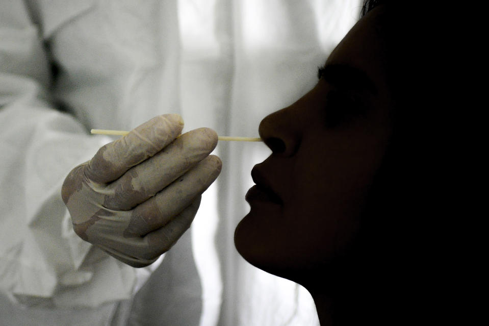 A doctor takes a nasal swab sample to test for COVID-19 at the Cocodrilos Sports Park in Caracas, Venezuela, Saturday, Sept. 19, 2020, amid the new coronavirus pandemic. (AP Photo/Matias Delacroix)