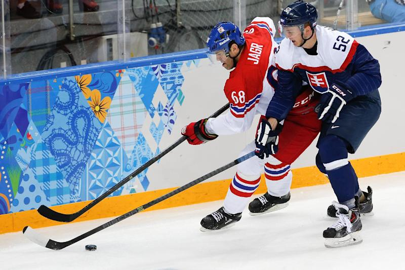 Czech Republic forward Jaromir Jagr and Slovakia defenseman Martin Marincin chase a loose puck during the first period of the 2014 Winter Olympics men's ice hockey game at Shayba Arena, Tuesday, Feb. 18, 2014, in Sochi, Russia. (AP Photo/Petr David Josek)