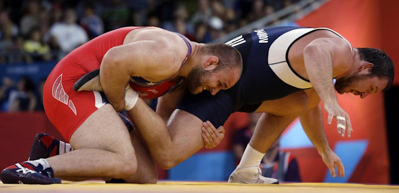 Tervel Ivaylov Dlagnev of the United States competes against Aleksei Shemarov of Belarus (in blue) during the men's 120-kg freestyle wrestling competition at the 2012 Summer Olympics, Saturday, Aug. 11, 2012, in London. (AP Photo/Paul Sancya)