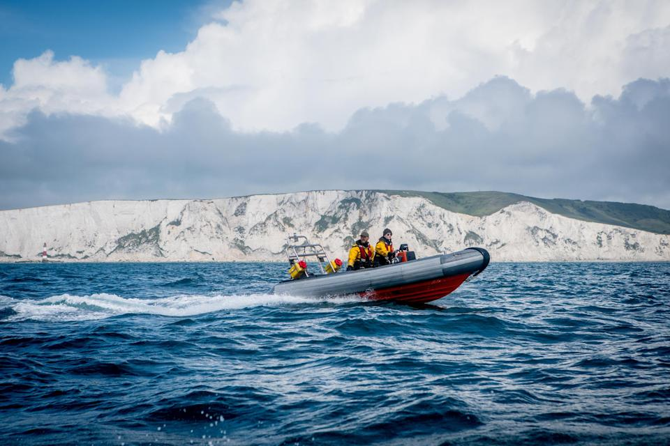 A Greenpeace rib in front of white cliffs in English Channel