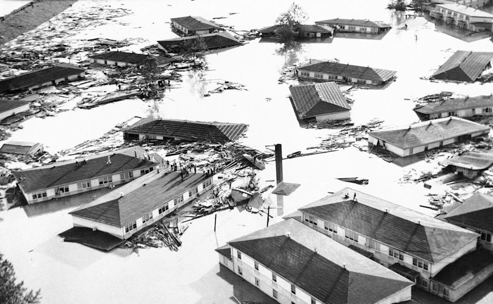 "People stand marooned on housetops in the community of Vanport, Oregon on May 30, 1948 while water swirls through debris of their town. <p class=""copyright""><a href=""https://newsroom.ap.org/detail/FloodUSOregonDestruction/58ec8d0199c54c3bb5b747f8ad14c715/photo?Query=vanport&mediaType=photo&sortBy=arrivaldatetime:desc&dateRange=Anytime&totalCount=9&currentItemNo=7"" rel=""nofollow noopener"" target=""_blank"" data-ylk=""slk:AP"" class=""link rapid-noclick-resp"">AP</a></p>"