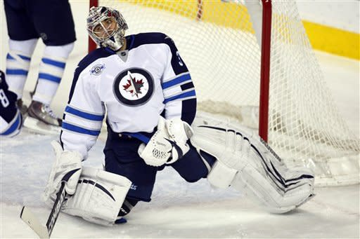 Winnipeg Jets goalie Ondrej Pavelec, from the Czech Republic, reacts to letting in the fifth goal during the third period of an NHL hockey game in Calgary, Alberta, Friday, March 9, 2012. The Flames won 5-3. (AP Photo/The Canadian Press, Jeff McIntosh)