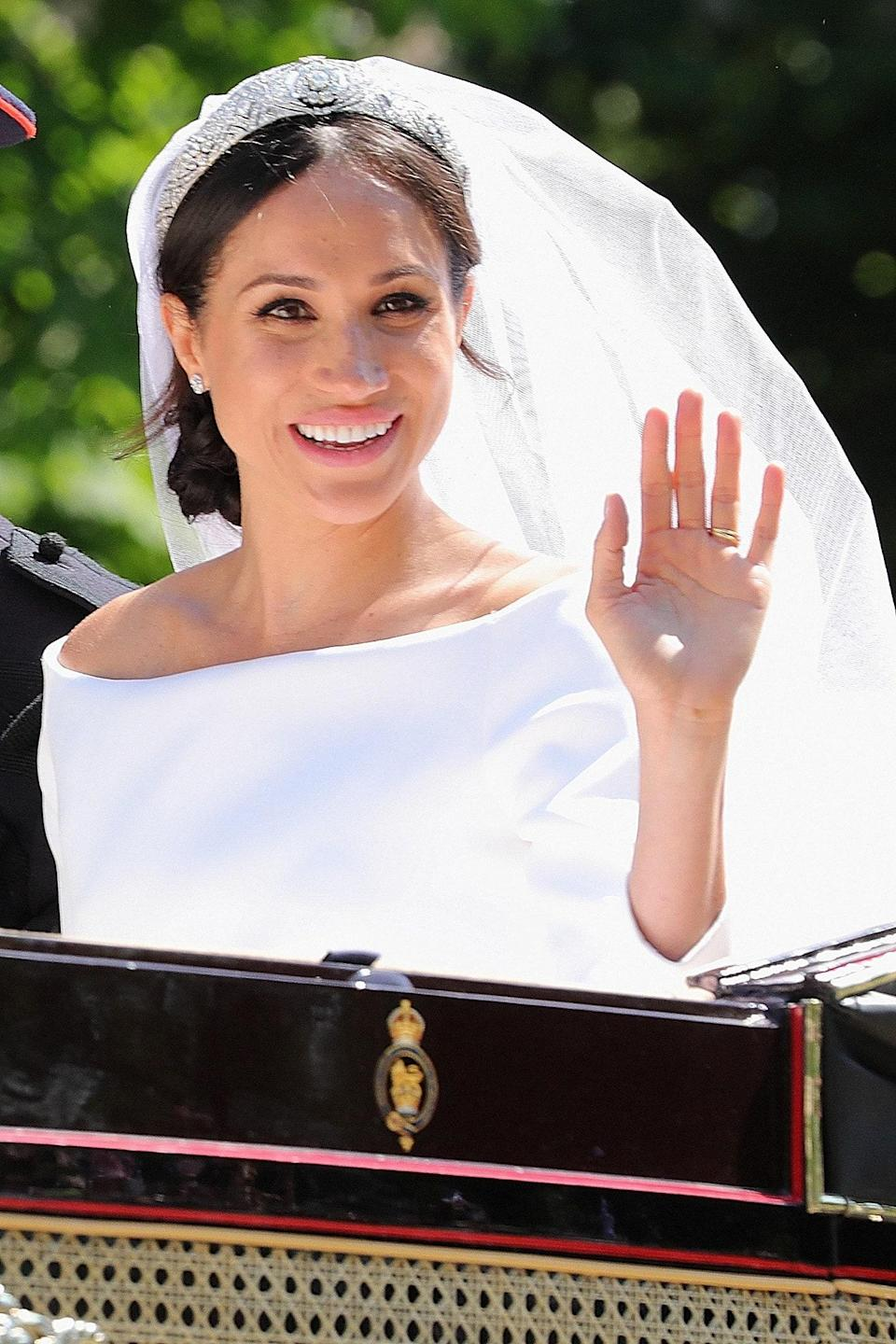 WINDSOR, ENGLAND - MAY 19: (EDITORS NOTE: Recrop of image 960063932.) Meghan, Duchess of Sussex leaves Windsor Castle in the Ascot Landau carriage during a procession after getting married at St Georges Chapel on May 19, 2018 in Windsor, England. Prince Henry Charles Albert David of Wales marries Ms. Meghan Markle in a service at St George's Chapel inside the grounds of Windsor Castle. Among the guests were 2200 members of the public, the royal family and Ms. Markle's Mother Doria Ragland. (Photo by Mark R. Milan/GC Images)