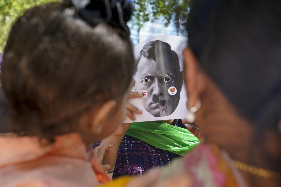 A demonstrator tries to scare a child while wearing a mask with a mash up photoshopped image of India's Prime Minister Narendra Modi and Adolf Hitler during rally in favor of Indian farmers outside the United Nations headquarters during the 76th Session of the U.N. General Assembly, Saturday, Sept. 25, 2021, in New York. (AP Photo/Mary Altaffer)