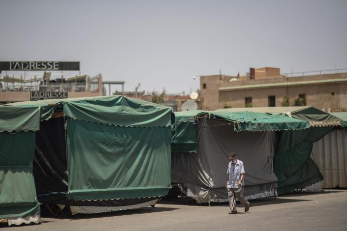 A man walks past empty stalls in the usually bustling landmark of Jemma el-Fnaa, in Marrakech, Morocco, Wednesday, July 22, 2020. (AP Photo/Mosa'ab Elshamy)