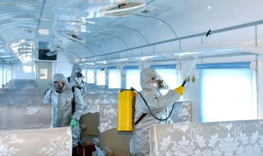Workers in protective suits spray disinfectant in North Korea