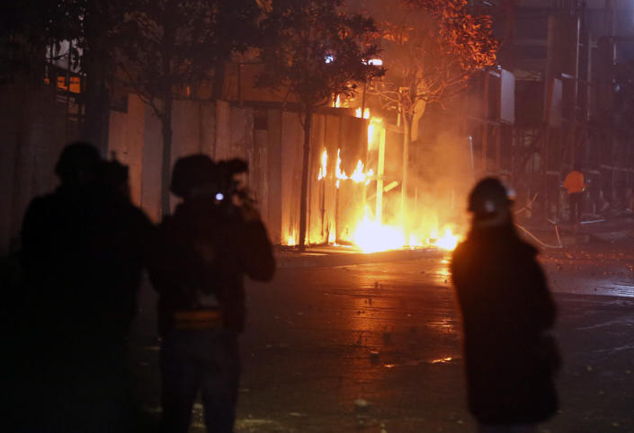 Hezbollah and Amal supporters set fire to trees in Beirut, Lebanon, Tuesday, Dec. 17, 2019. Supporters of Lebanon's two main Shiite groups Hezbollah and Amal have clashed with security forces and set fire to cars in Beirut in a third consecutive night of violence in the capital. The unrest early Tuesday apparently was triggered by a video circulating online that shows a man insulting Shiite and religious figures. (AP Photo/Bilal Hussein)